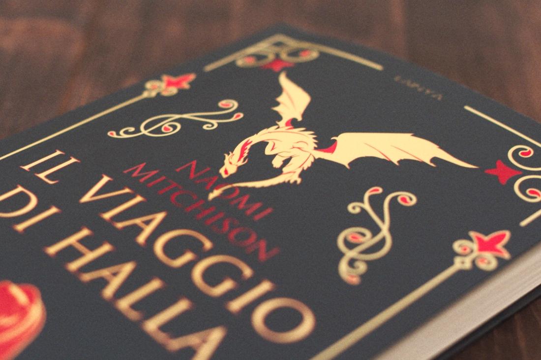 copertina blu con drago giallo e orsa rossa, decori medievalegganti, il titolo del libro è il viaggio di halla scritto da naomi mitchinson